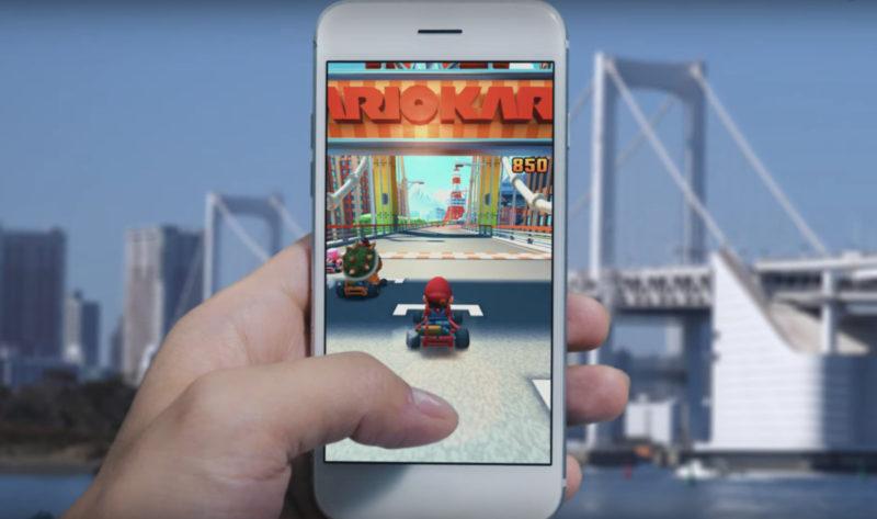 Pessoa segurando um celular com o jogo Mario Kart rodando.