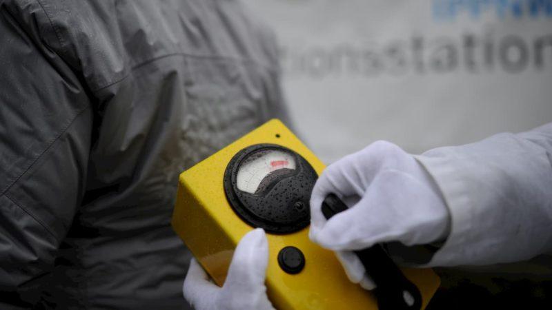 Medidor de radiação. Foto mostra um aparelho retangular amarelo com um mostrador redondo com ponteiro seundo segurado por uma mão com uma luva branca.