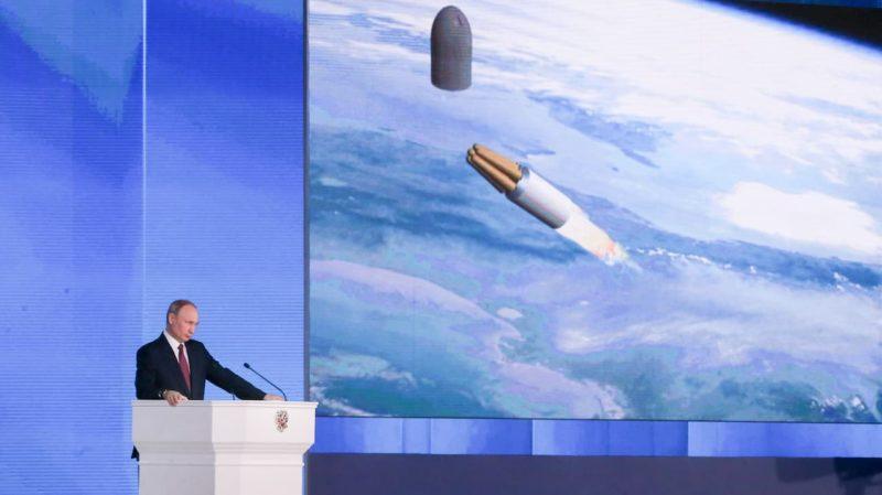 Presidente da Rússia, Vladimir Putin, em uma tribuna. Ao fundo, uma tela mostra a imagem de um míssil voando em uma grande altitude.