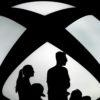 Logo do Xbox com silhuetas de uma família em frente dele.