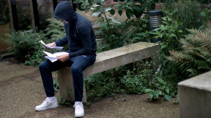 Jovem usando moletom e tênis sentado no banco de uma praça vendo papéis, presumivelmente de contas a pagar.