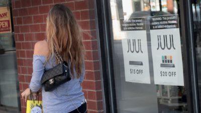 Mulher de costas passando em frente a uma loja da Juul