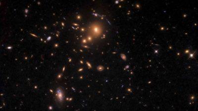 Imagem de aglomerado de galáxias mostra pontos luminosos alongados.