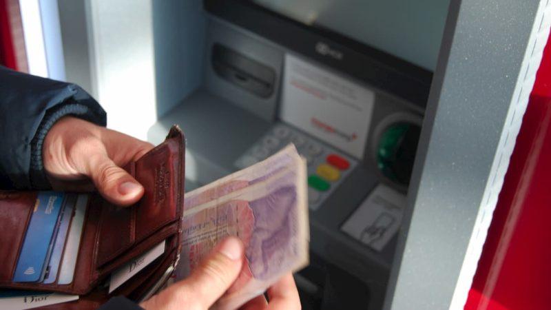 Pessoa conta dinheiro em frente a um caixa eletrônico.
