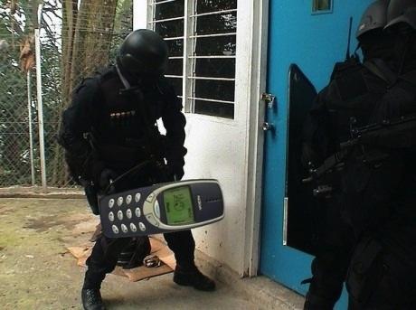 Meme de um policial tentando arrombar uma porta com um Nokia
