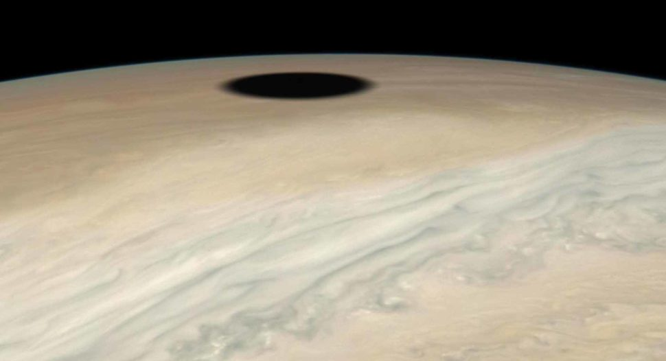 Imagem da superfície de Júpiter mais próxima e perpendicular, com om tons mais acinzentados e amarelados, e um círculo preto próximo ao horizonte.