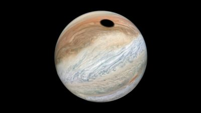 Júpiter (uma esfera com nuvens acinzentadas e avermelhadas) com um círculo preto na parte superior.