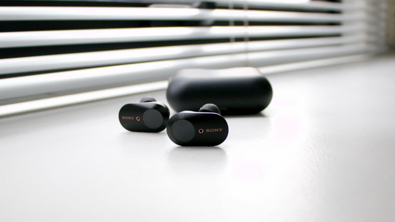 Fones de ouvido Sony WF-1000XM3 ao lado de sua caixinha para carregamento