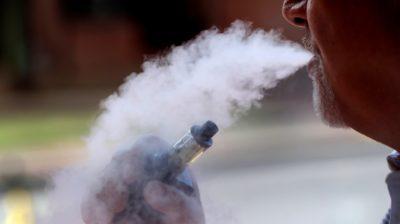 Homem expelindo fumaça após usar cigarro eletrônico/vaporizador