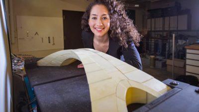 Estudante posa ao lado de réplica feita em impressora 3D de desenho de ponte concebido por Leonardo Da Vinci