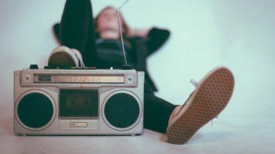 Jovem deitado com um pé sobre um rádio antigo.