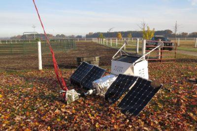 Aparelho parecido com satélite, mas com materiais claramente mais comuns e menos resistentes, caído no chão de uma fazenda.