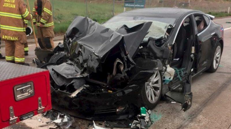 Carro elétrico da Tesla com a frente retorcida depois de colidir com um carro dos bombeiros.