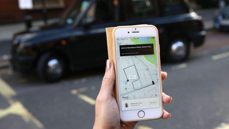Aplicativo da Uber em frente a um táxi de Londres