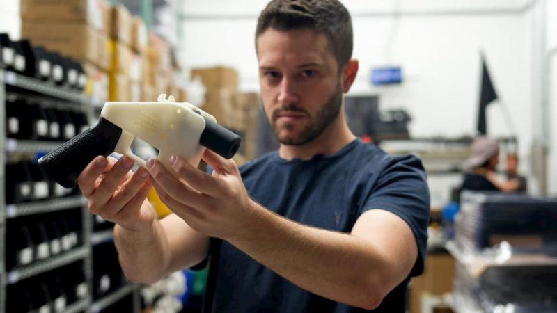 Pessoa segurando uma arma de fogo impressa em 3D