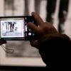 Pessoa tirando foto de um quadro com um smartphone
