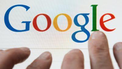 Dedos sobre o logotipo do Google em um computador