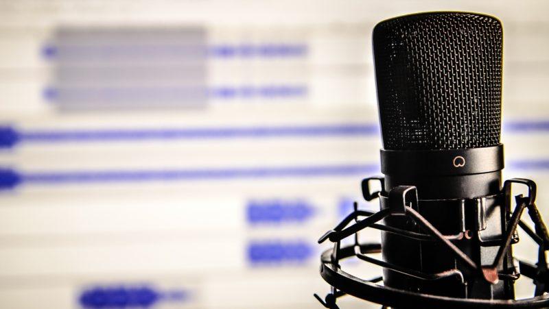Microfone com trilhas de áudio exibidas em tela de computador em segundo plano