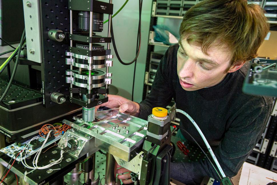 James Clegg, cientista óptico sênior da Microsoft, coloca um pedaço de vidro em um sistema que usa inteligência artificial e tecnologia óptica para recuperar e ler informações no vidro. Crédito: Jonathan Banks/Microsoft