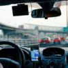 Motorista de Uber com passageiro no carro e smartphone no painel