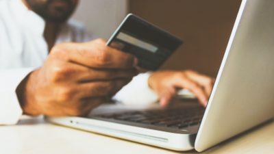 Pessoa segurando cartão de crédito em frente a um laptop