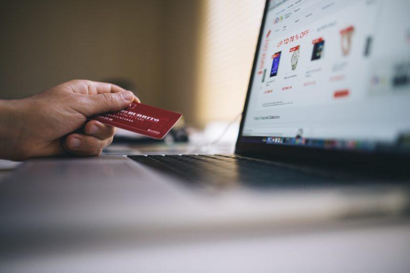 Mão segurando cartao de crédito em frente a laptop