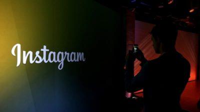 Uma pessoa tirando foto do logotipo do Instagram