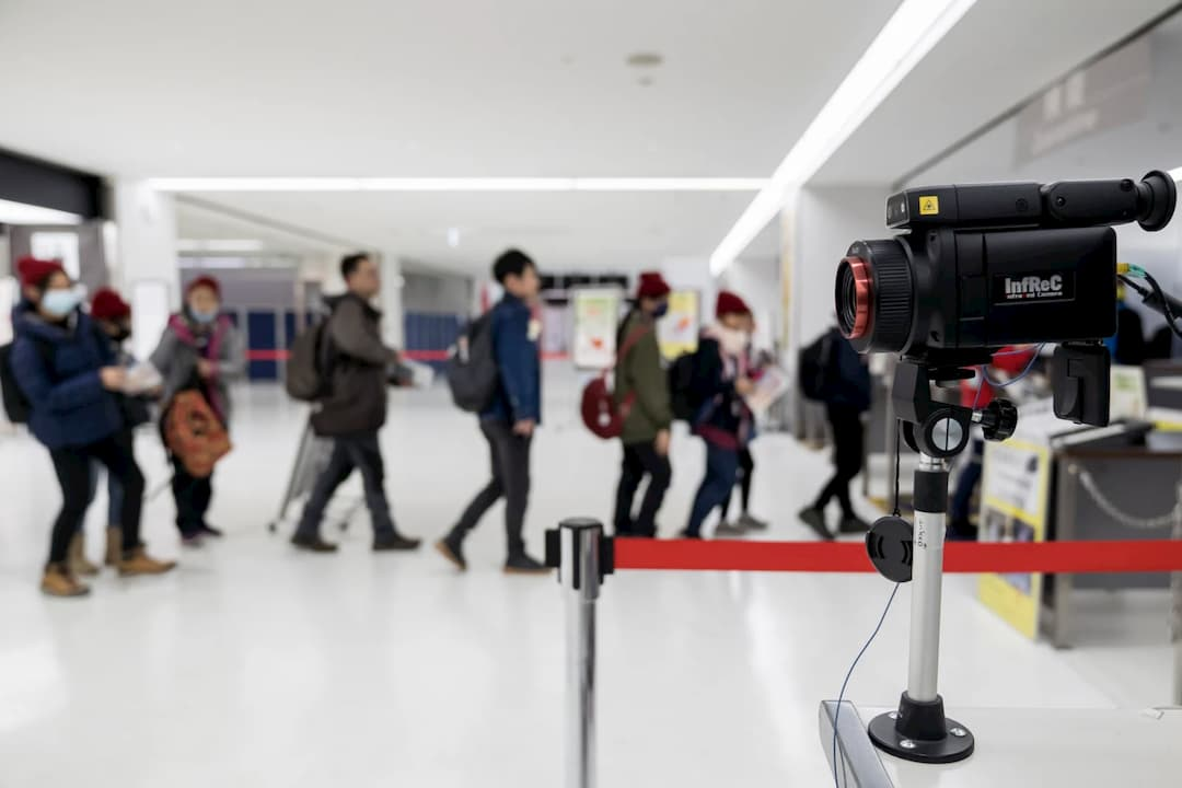 Viajantes passam por um scanner térmico durante a chegada ao aeroporto de Narita, em 17 de janeiro de 2020, no, Japão