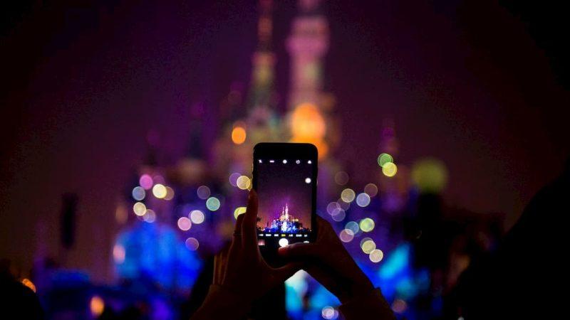 turista tira uma foto com um iPhone na Disneylândia de Xangai.