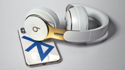 Montagem com traseira de um smartphone com o logo do Bluetooth e um fone Beats