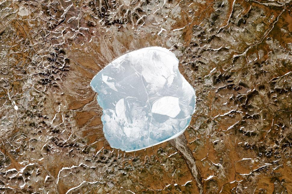 Imagem de satélite de cor natural do Lago El'gygytgyn, que fica dentro de uma pequena cratera de impacto asteróide no leste da Rússia, perto do Círculo Ártico. A cratera de impacto tem cerca de 3,6 milhões de anos