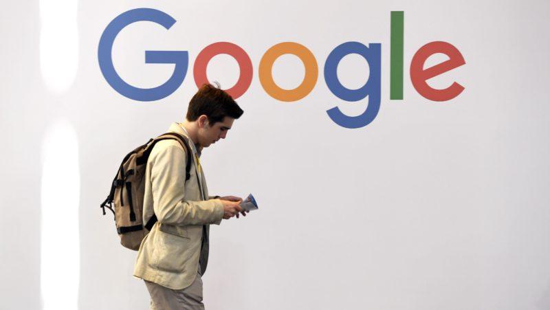 Homem passa em frente ao logotipo do Google. Crédito: Getty
