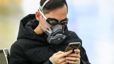 Homem se protege do coronavírus com máscara no rosto e óculos de natação enquanto usa o celular