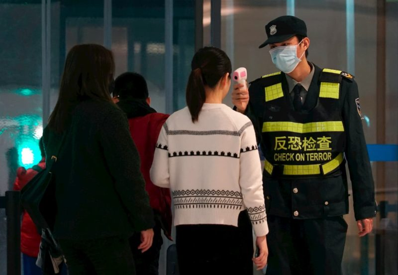 Funcionário de um aeroporto usa uma pistola de temperatura para verificar as pessoas que saem do Aeroporto Internacional de Wuhan Tianhe estão com febre