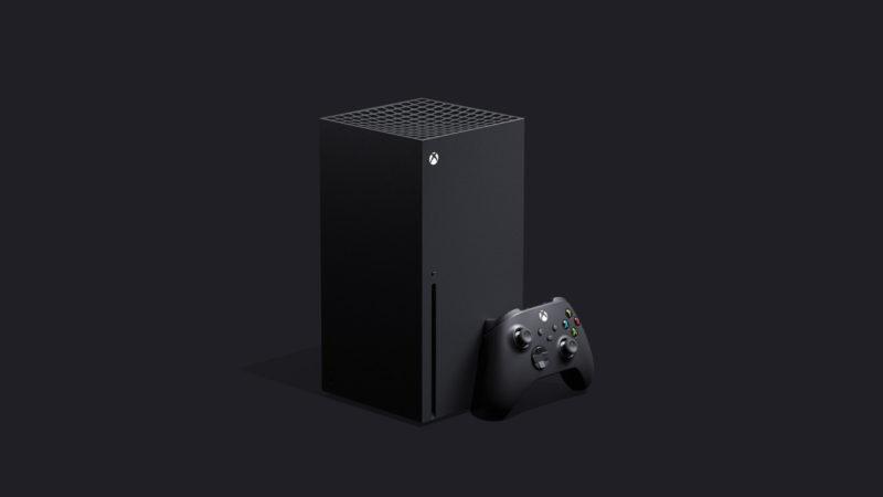 Imagem de um Xbox Series X: uma caixa preta retângular, com um joystick apoiado nela.