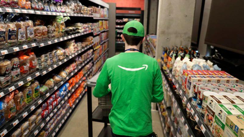 Pessoa com camiseta da Amazon passeia na loja Go Grocery