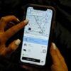 Mulher interagem com smartphone com app da Uber aberto