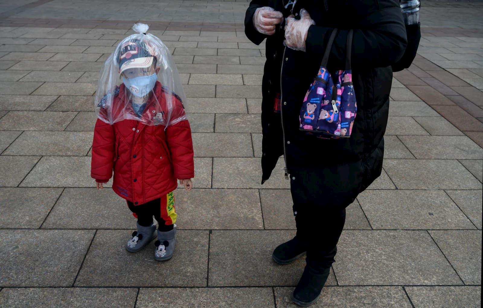 Um menino chinês coberto por um saco plástico em Pequim