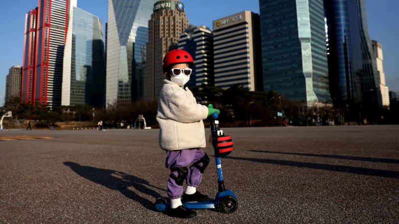 Criança de touca, óculos escuros e máscara cirúrgica. A criança está sobre um patinete. Ao fundo, vários prédios.