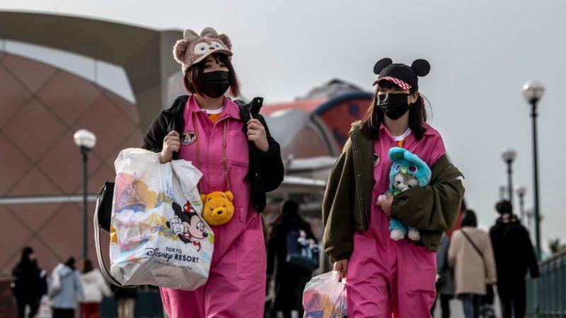 Mulheres usando máscaras descartáveis saem da Disneylândia de Tóquio