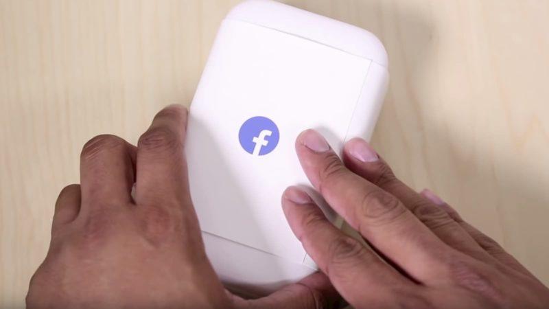 Pessoa mexendo em uma caixa com logo do Facebook