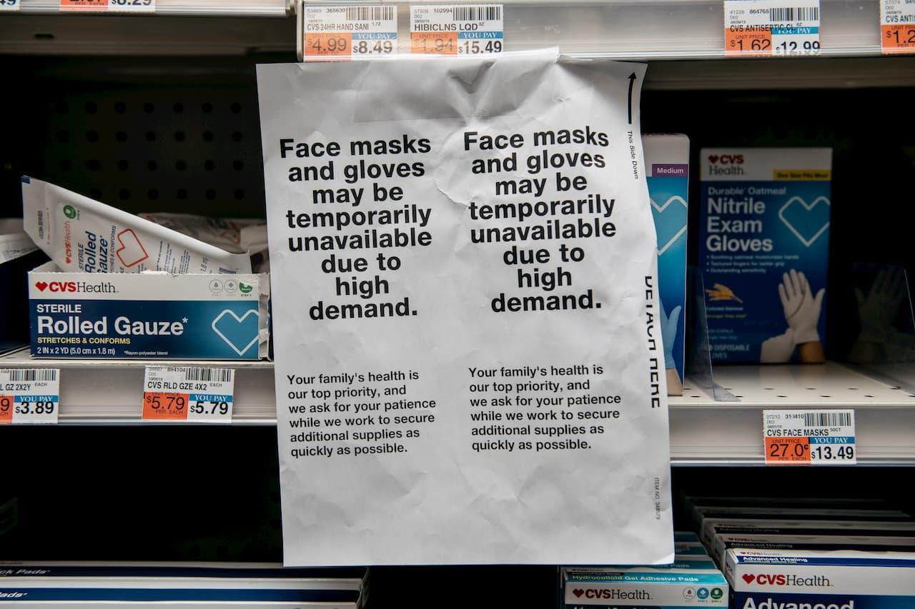 Aviso em farmácia dizendo que há falta de máscaras.