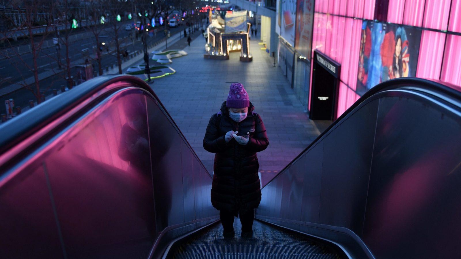 Mulher com máscara sobe escadas rolantes