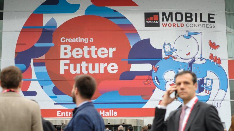 Pessoas em frente a painel do Mobile World Congress 2018