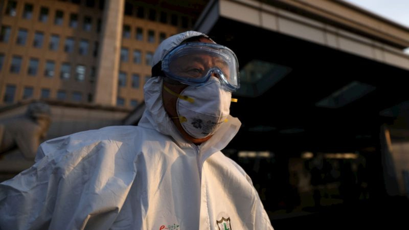 Trabalhador de saúde na Coreia do Sul se prepara para desinfetar o edifício da Assembleia Nacional em Seul
