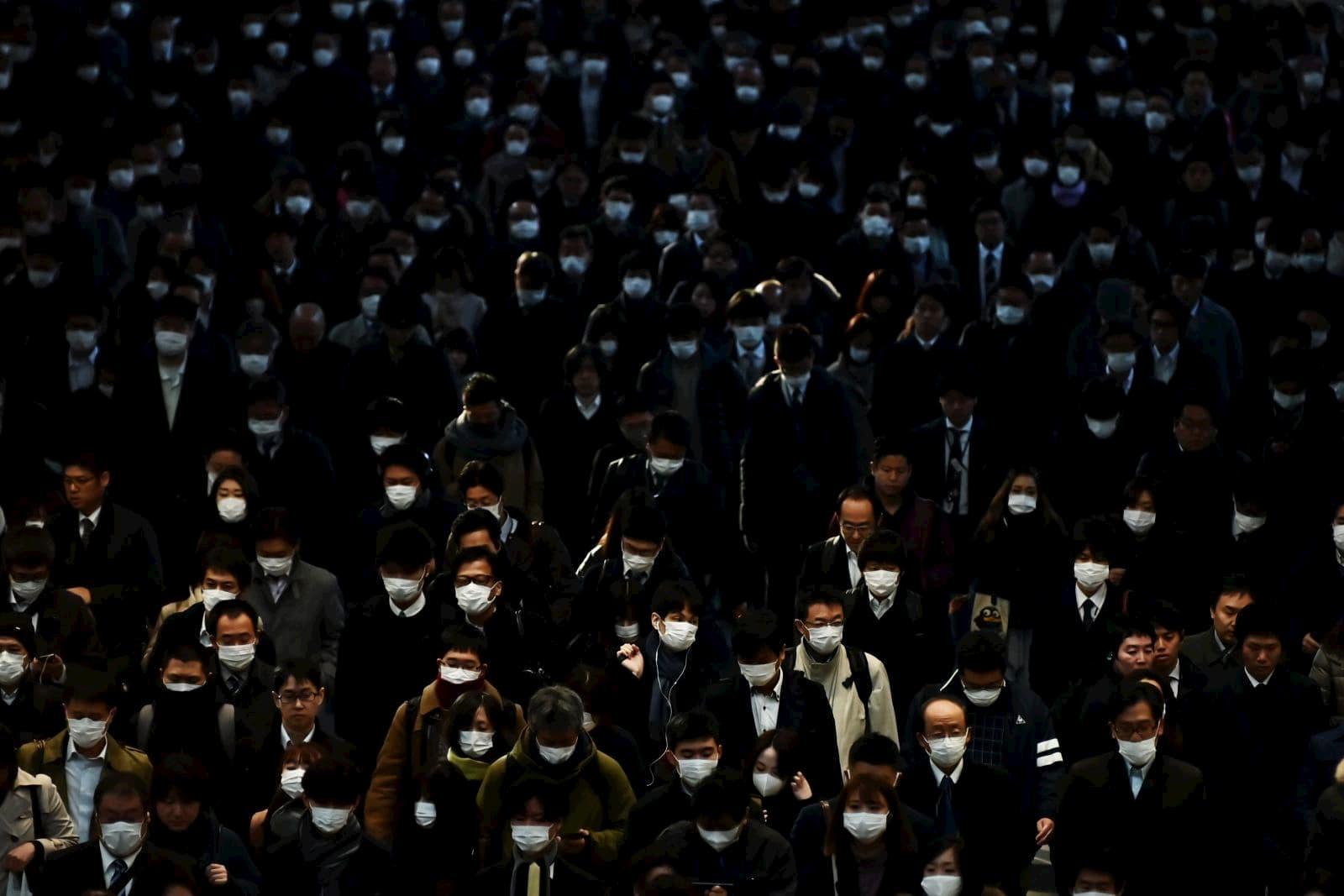 Pessoas usam máscaras para ir ao trabalho durante o horário de pico de Tóquio