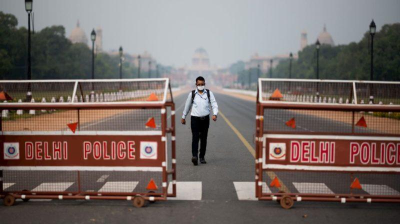 Homem caminha em rua deserta que leva ao Palácio Presidencial de Nova Deli, Índia