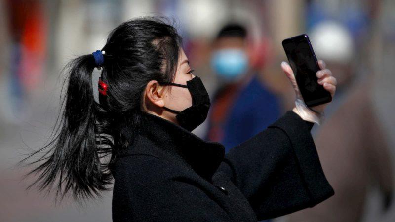 Mulher com máscara usando celular