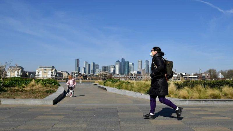Mulher com máscara caminha em Greenwich, Londres