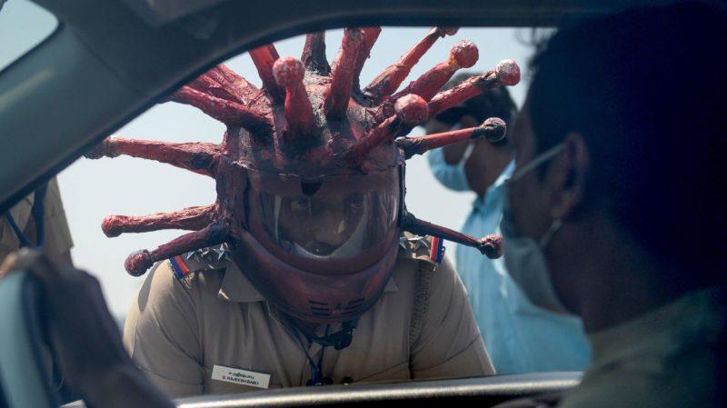 Policial Rajesh Babu vestindo um capacete com o formato do coronavírus, enquanto fala com um motorista em Chennai em 28 de março. Crédito: Getty Images